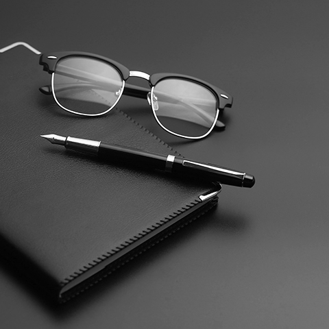 fountain pen and glasses resting on a leather notebook