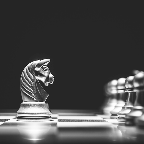 closeup on chess board with knight facing a row of pawns