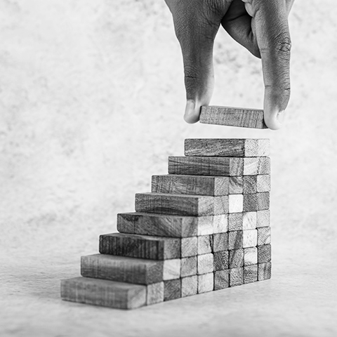 hand stacking blocks into a staircase